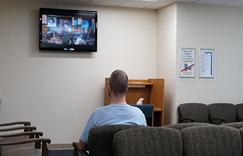 Man watching Digital Signage in Va Hospital Waiting Room
